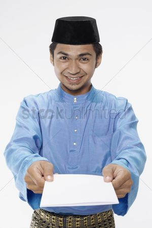 Baju melayu : Man in traditional clothing presenting blank greeting card