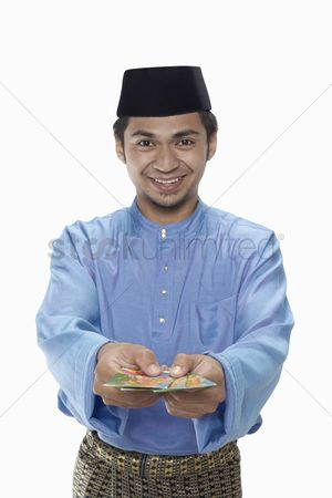 Baju melayu : Man in traditional clothing presenting green packets