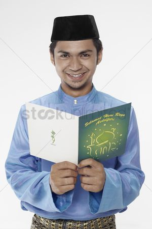 Baju melayu : Man in traditional clothing reading greeting card