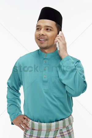 Baju melayu : Man in traditional clothing talking on mobile phone