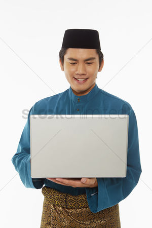 Baju melayu : Man in traditional clothing using laptop
