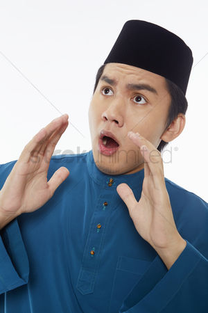 Baju melayu : Man in traditional clothing with a shocked facial expression