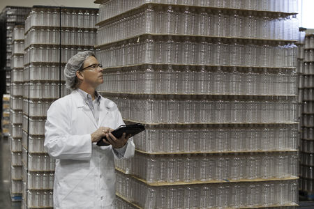 Pile : Man inspecting bottled water in distribution warehouse