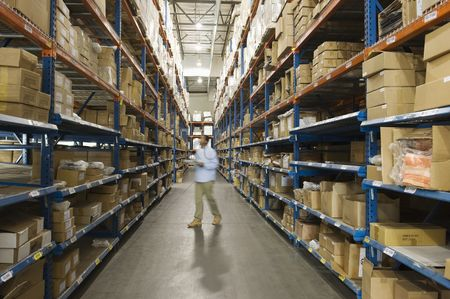 Mid adult man : Man inspecting boxes in distribution warehouse