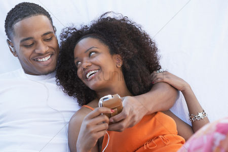 Relationships : Man listening to mp3 player hugging girlfriend