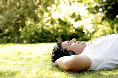 Grass : Man lying on the grass listening to music on the headphones