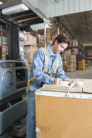Notepad : Man making notes in distribution warehouse