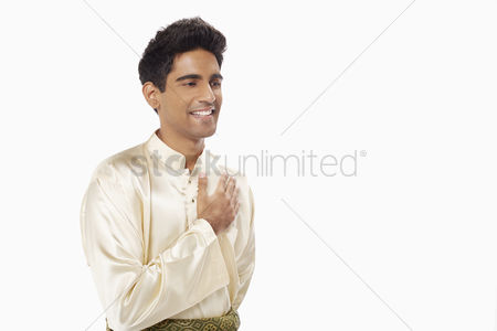 Baju melayu : Man placing hand on chest  showing greeting gesture