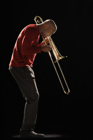 Blowing : Man playing trombone side view