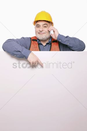 Cheerful : Man pointing at placard while talking on the mobile phone