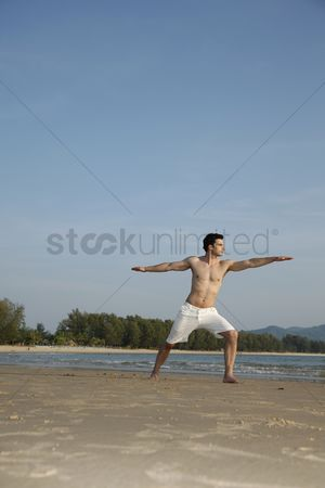 Practising yoga : Man practising yoga on beach
