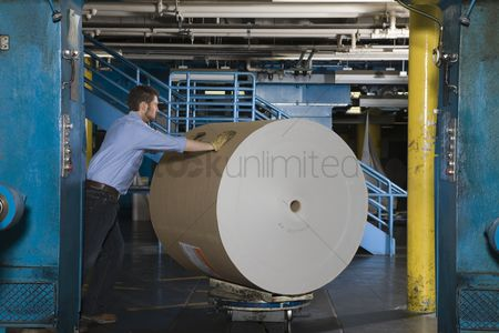 Pushing : Man pushing huge roll of paper in newspaper factory
