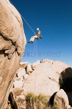 Rope : Man rappelling on cliff side view