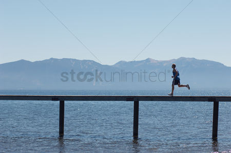 Fitness : Man running along pier with mountains behind side view