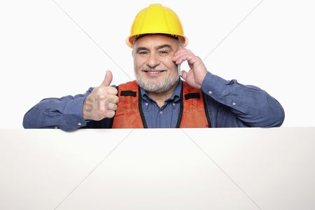 Leadership : Man showing thumbs up while talking on the mobile phone