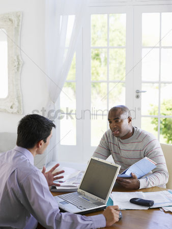 Sitting on lap : Man sitting at dinning table with financial advisor