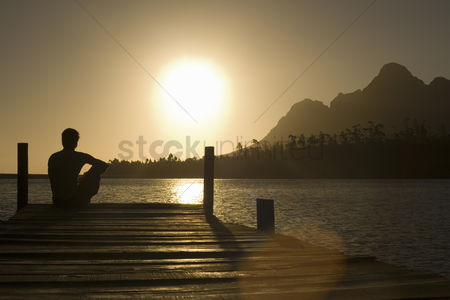 One person : Man sitting on dock by lake back view