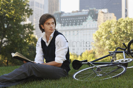 Wondering : Man sitting on lawn holding book
