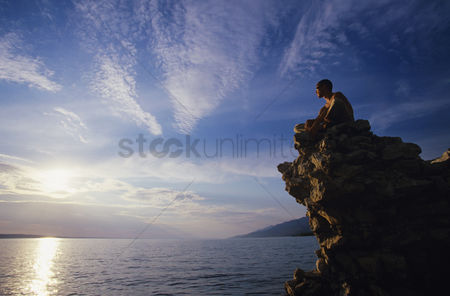 Contemplation : Man sitting on rock overlooking ocean