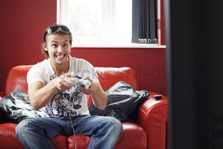Excited : Man sitting on the couch playing video game console