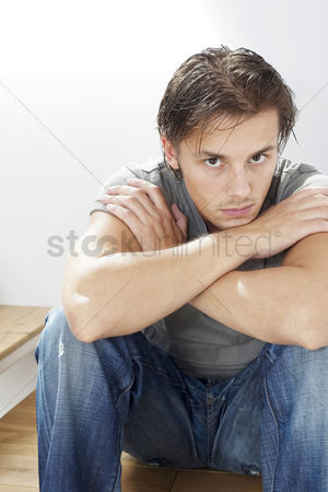 Composed : Man sitting on the staircase staring at the camera