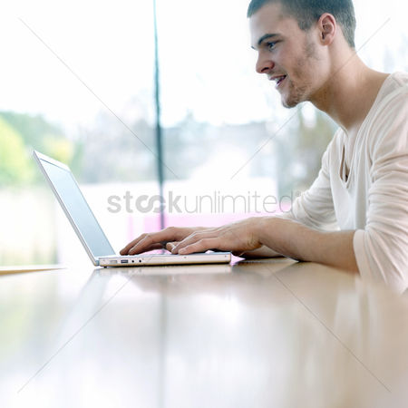 Enjoying : Man smiling while using laptop