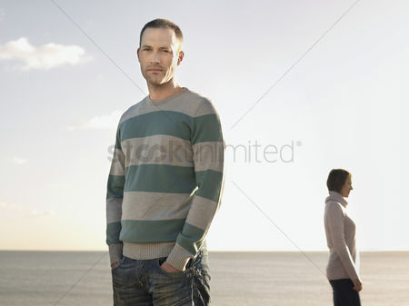 Pocket : Man standing on beach with woman in background portrait