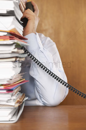 Pile : Man talking on telephone mid section behind stack of paperwork at desk