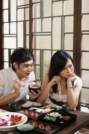 Ignorance : Man trying to feed his sulking girlfriend