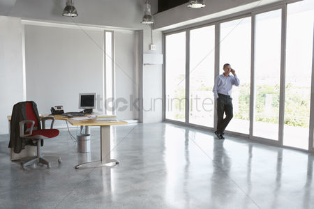 Pocket : Man using mobile phone leaning against window in empty office building