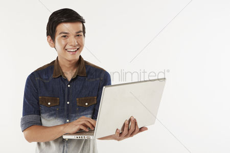 Portability : Man using the laptop while standing