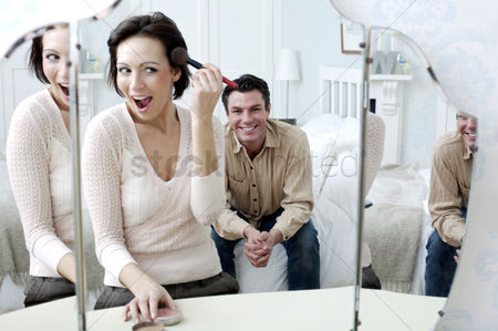 Attraction : Man watching his wife looking at the mirror applying make-up