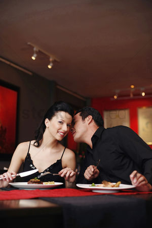 Celebrating : Man whispering into his girlfriend s ear while having dinner in a restaurant