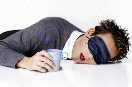 Enjoying : Man with eye mask sleeping with the head on the table