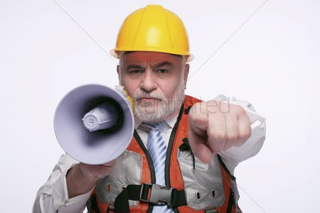 Leadership : Man with hardhat pointing while shouting into megaphone