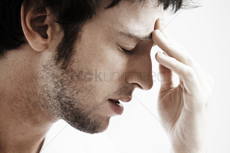 Head shot : Man with headache touching forehead close up