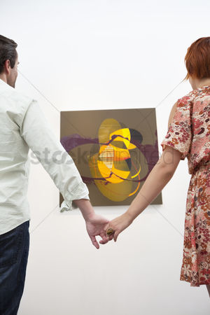 Interior background : Married couple holding hands in front of painting in art gallery