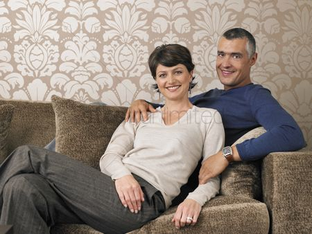 Wallpaper : Married couple relaxing on sofa