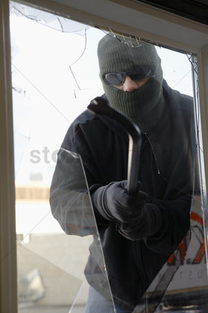 Thief : Masked thief braking glass with crowbar