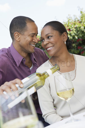 Wine bottle : Mature man pouring wine for his elegant wife