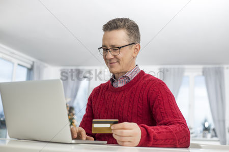 40 44 years : Mature man using credit card and laptop to shop online during christmas