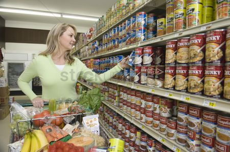 Supermarket : Mature woman selects tinned goods in supermarket aisle