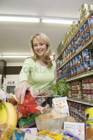 Supermarket : Mature woman with grocery shopping in supermarket aisle