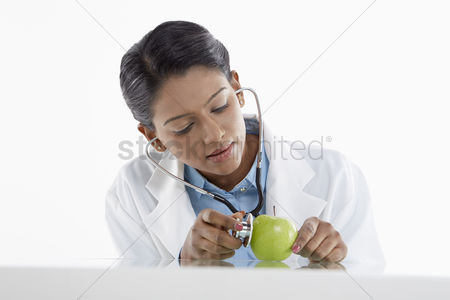 Malaysian indian : Medical personnel examining a green apple