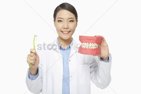 Tooth brush : Medical personnel holding up a tooth brush and a set of dentures