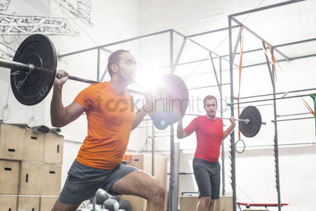 Muscle training : Men lifting barbells in crossfit gym
