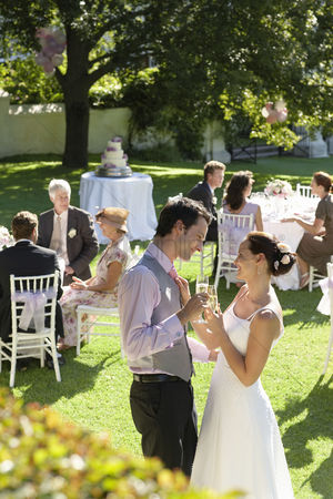 Dance : Mid adult bride and groom in garden toasting among wedding guests