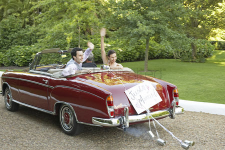 Car : Mid adult bride and groom in vintage car waving hands