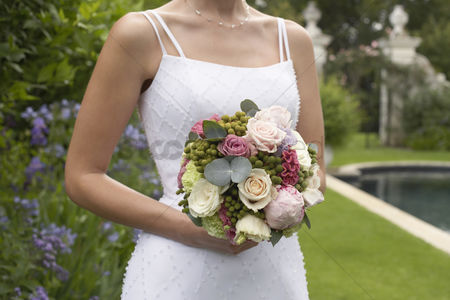 Summer : Mid adult bride at poolside holding bouquet mid section