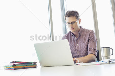Internet : Mid-adult businessman working laptop at desk in creative office